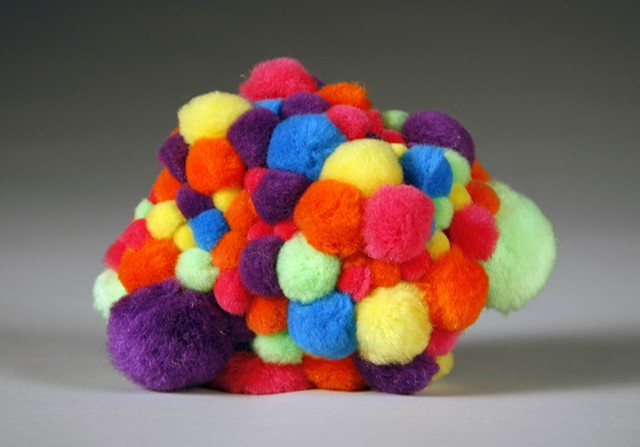 rainbow multicolored pom poms on found rock by Holly Campbell