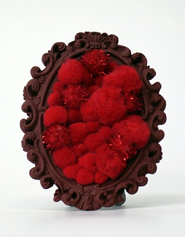 found oval picture frame sculpture painted filled with rainbow colored shiny red pom poms by Holly Campbell