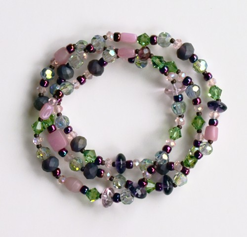 beaded bracelet in swarovski glass, and glass beads in light pinks, purples, and light or pale green with stretch cord