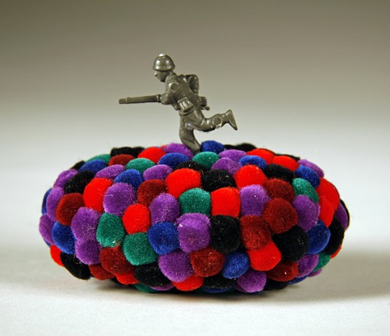 found rock sculpture covered in purple red turquoise green maroon and black pom poms running toy army soldier on top by Holly Campbell