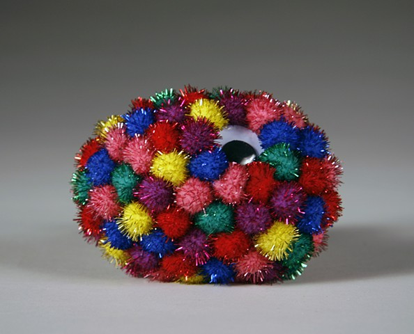 found rock sculpture covered in one large wiggle eye and rainbow shiny pom poms by Holly Campbell