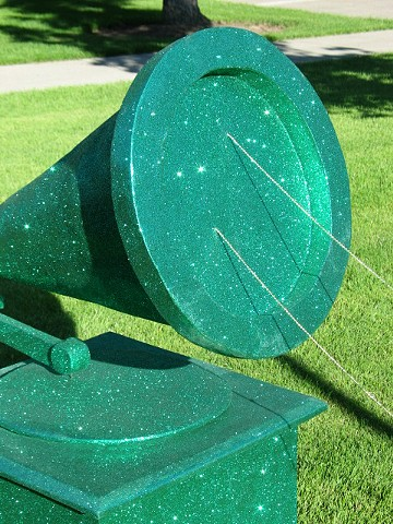 sculpture giant green phonograph covered in green glitter with gold bead string connecting to a pink phonogrtaph by Holly Campbell