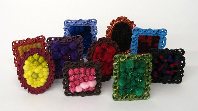 found picture frame sculptures painted filled with rainbow colored yarn pom poms by Holly Campbell