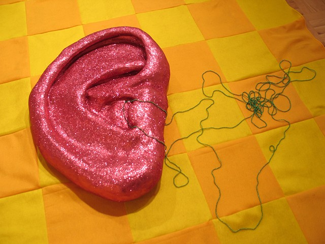 sculpture pink glittered ear ceramic green strings of beads coming from it on checkerboard felt background by Holly Campbell