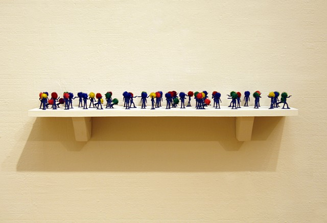 plastic police officer toy sculptures with shiny rainbow pom poms heads shelf by Holly Campbell