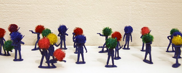 plastic police officer toy sculptures with shiny rainbow pom poms heads by Holly Campbell
