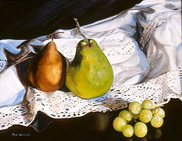 A brown and yellow pear both sit on a white cloth with lace.  Green grapes sit on a mahogany surface