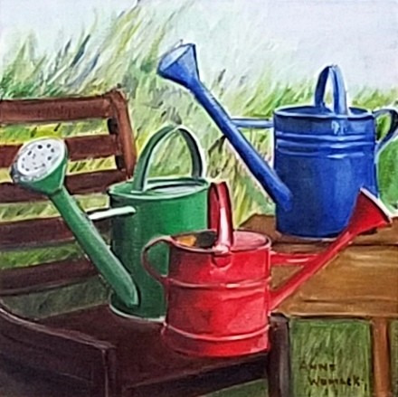 Green, Red, and Blue watering cans in a garden.  Brown chair and table