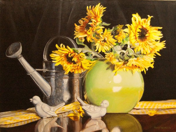 A galvanized watering can sits behind a lime green vase filled with sunflowers. The vase, two white porcelain birds and a yellow checked cloth reflect on the surface.  Colors pop against the black background.