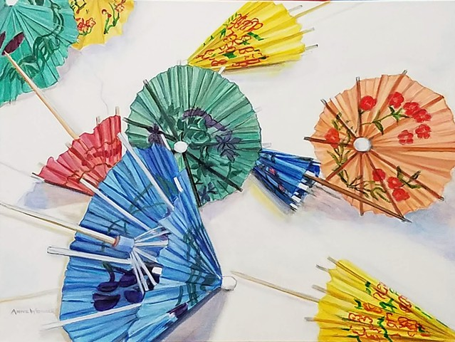 Colorful paper cocktail umbrellas tossed on a white background