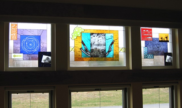 "Cafeteria windows with imagery including an atom,  giant tube worms, map of Atlantis, a DNA double helix, illustration from Jules Verne's ""A Walk Under the Waters"", satellite dishes that are part of Allen Array"