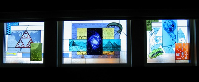 Cafeteria windows including images of our galaxy, Sierpinsky triangle, illustration from Jules Verne book, Burgess shale creatures, Atlas holding up our planet, Arecibo message