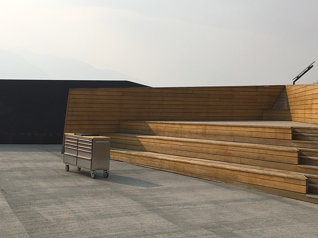 Lonely empty auditorium at Glacier Skywalk; grey sky; wooden seats