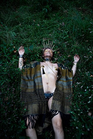 Echo, a light skin person with long brown hair pulled back, sits next to a fallen tree and tall grass. He is covered in gold and wearing a handmade gold textile ruana, syringe halo crown and testosterone bottle rosary. He also wears large hoop earrings, a