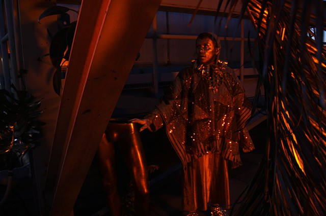 The scene is dark and the details are orange-tinted gold. Echo has one hand on a pair of gold mannequin legs and is looking at a plant behind a rafter. He is wearing a triangle gold sequin patterned ruana with necklaces made of gold leafed medical vials,