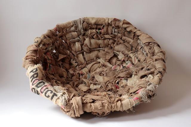 "A large round textile comprised of woven strips of burlap coffee sacks into a papasan chair. The bottom right strip of burlap reads ""Product""."