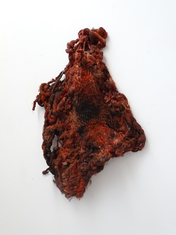 A knit wool sculpture hangs diagonally from one of its four cornes. The object is covered in oil paint with fleshy hues of red and black. The fabric is tightly knit in some areas and unravelling around the edges.