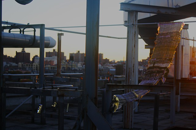 A textile hangs from a pipe with the sunsetting to its right on an industrial rooftop. The cityscape is visible in the background. The textile is comprised of golden fabric, wool, hemp, Colombian flags, camo print and fishnet. To the right there are small