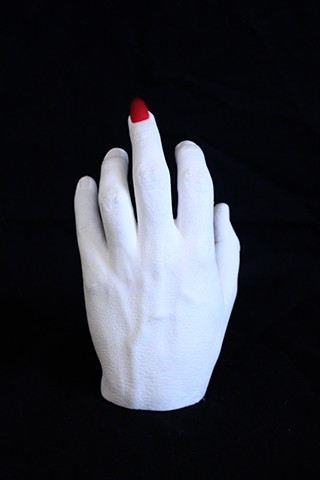 Plaster hand cast with red acrylic nail on the middle finger