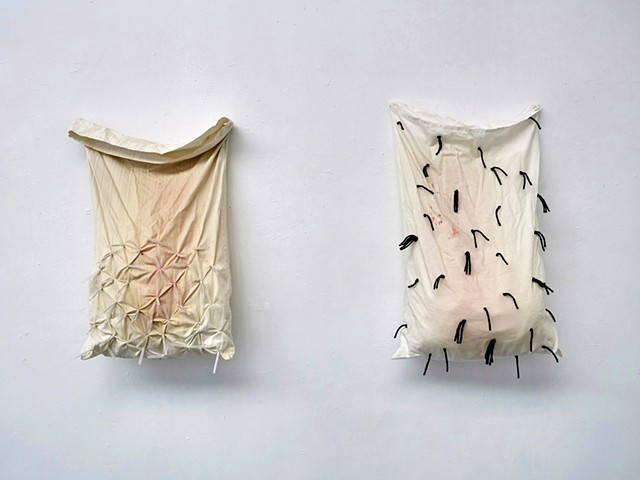 Two pillowcases are hung vertically on a white wall both white with pale red stains, the left has injection needles (with caps on) stuck through the bottom half of the fabric and the right has short strands of black yarn speckling the pillowcase. The bot