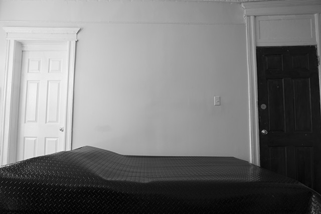 A grey-scale photograph. Black diamond plated rubber flooring lies on top of a bed, The bed is horizontal in the frame, and no bed frame can be seen. On the left of the image, the covered bed.bulges where pillows are usually placed. It is against a bedroo