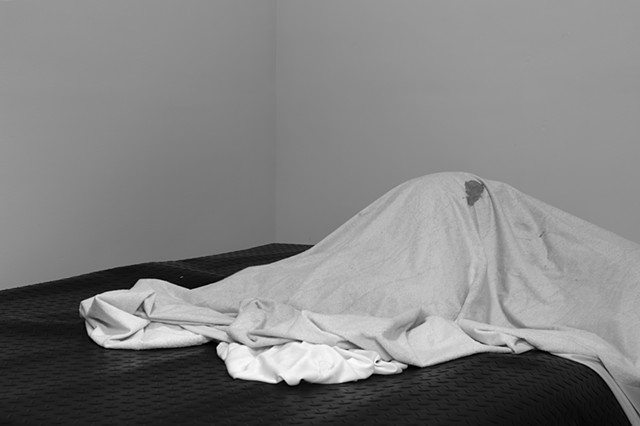 A grey-scale photograph. Black diamond plate rubber flooring covers a bed. Behind the bed are blank walls. On top of the rubber covered surface is a figure hidden underneath bedding with a visible stain. The silhouette of the figure is abstracted by the d