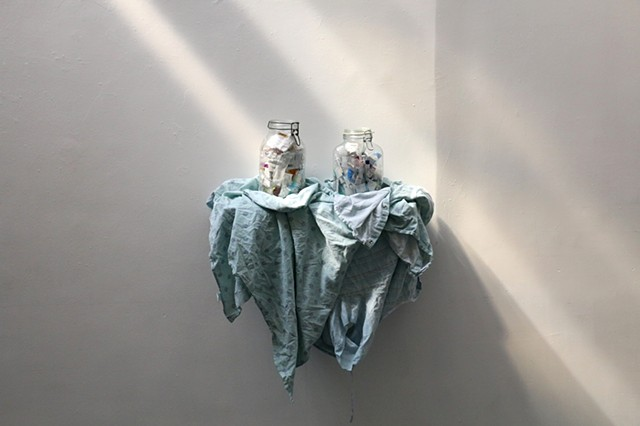 Two glass jars sit side by side on a shelf draped with medical gowns. The jars contain an array of medical ephemera including used needles and prescription bottles. The piece is installed on a white wall. Coming in like a dream from the upper left at an a