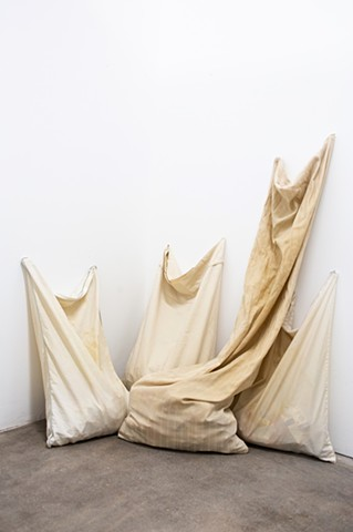 Four pillowcases, stained from use, sit vertically huddled together in a corner, on a brownish grey concrete floor. They lean against white walls, reaching upwards. One pillowcase is the size of a long body pillow. They are filled with medical ephemera wh
