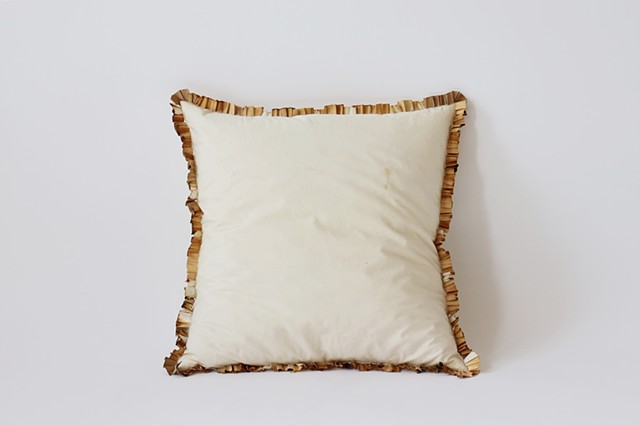 A square throw pillow lies upright against a white background. The pillow is off white with marks from use. Wrapped around the entirety of the seams are unraveled and pleated joint filters sewn into the pillow. They are a range of sh