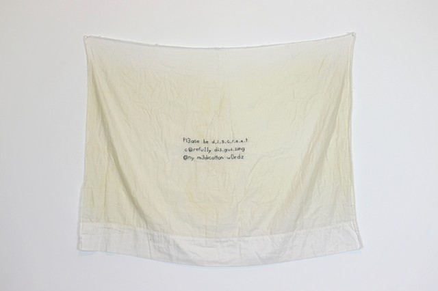 A pillowcase, once white now seeped with sweat stains, hangs on a white wall. It has been split open and appears as a continuous sheet of fabric. In the center of the fabric is small text stitched in black thread. It reads: (first line) Pl3ase be d.i.s.c.