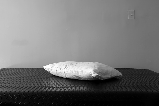 A grey-scale photograph. Black diamond plated rubber flooring lies on top of a bed, however the crop of the frame cuts off the bottom and ends of the bed turning it into a shiny textured surface. On top lies a pillow and the background only contains a lig
