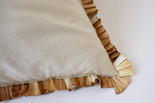 A close up of the bottom right corner of an off-white square throw pillow without a pillow case lies against a white background. Sewn into the seams of the pillow are unraveled and pleated joint filters. They are a range of shades, white, tan and differen