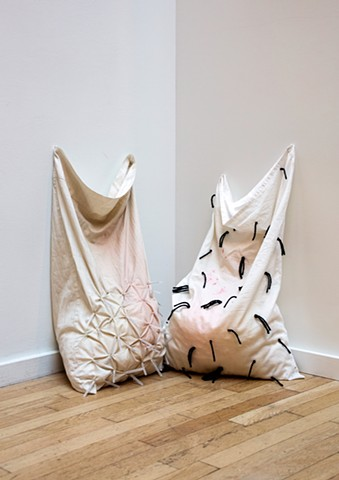 Two pillowcases sit in a corner on a wood floor against a white wall. Both are white with pale red stains, the left has injection needles (with caps) stuck through the bottom half of the fabric and the right has short strands of black yarn speckling the