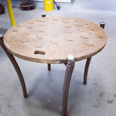 Salvaged manhole cover with heavy steel welded legs