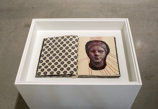 Exhibition view of Notations. Notations is a one of a kind artist's book by Dianna Frid, made with cloth, photographic transfers, and thread. The book focuses on the cloth and hairstyles carved in Greco-Roman Sculpture