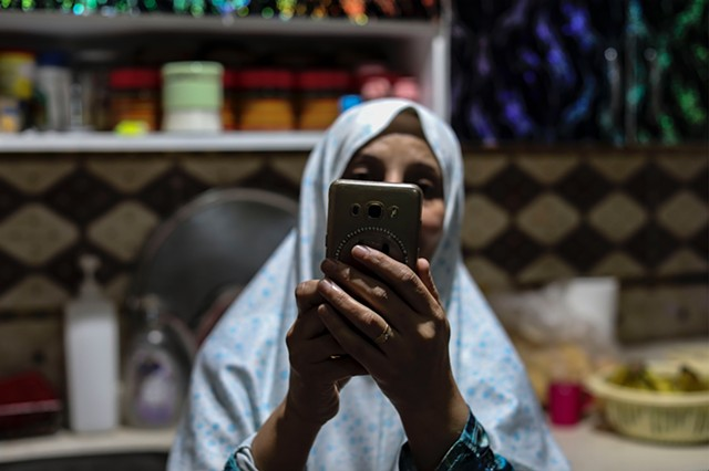 Baheya, Hala's mother, video chats with her eldest daughter, Hadice, who lives in Idlib, Syria. Baheya and Abu Mahmoud have been married for 18 years and live with four of their five children.