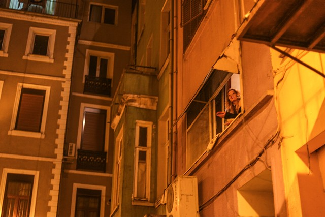 In a neighboring area outside of Taksim Square in Istanbul, Turkey, a prostitute casually hangs out of the window of a brothel, often a means of acquiring late night customers. The majority of Istanbul's legal brothels were closed in January 2013.