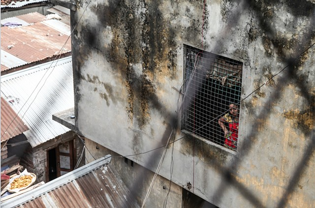 A young sex worker stares outside of a hallway window at the Rathkhola Brothel in Faridpur, Bangladesh.