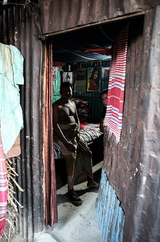 A sex worker peeks out of her room at the C&B Ghat Brothel in Faridpur, Bangladesh after finishing with a customer. Independent prostitutes (those without madams) must pay rent on their own rooms.