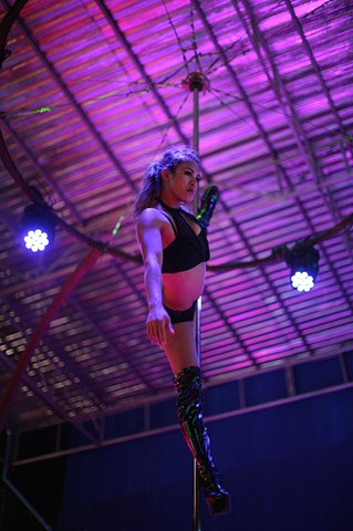 A dancer entertains tourists at an outdoor strip club in Phuket, Thailand. In contrast to Bangkok, Phuket accepts prostitution more openly because of its longstanding reputation as a resort.
