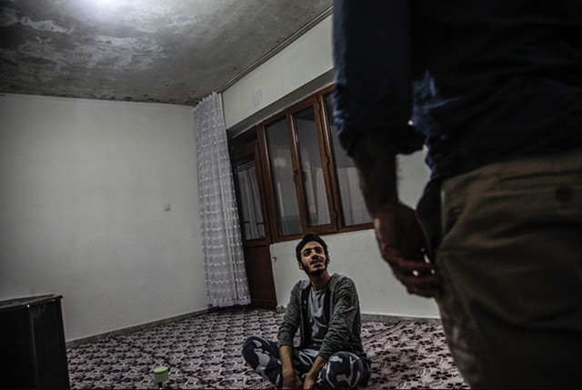 Mahmoud, 19, welcomes a visitor into the family home.