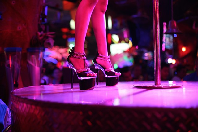 A young exotic dancer gets ready for a performance at a strip club in Phuket, Thailand.