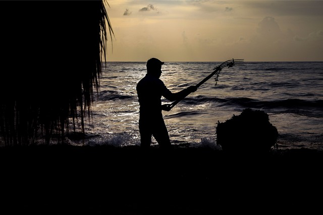 Oscar,* a migrant worker originally from Chiapas, Mexico, rakes away seaweed that has amassed overnight in front of a luxury hotel and resort in Sayulita, Mexico. He travels to the region seasonally along with the majority of the men who do this work.