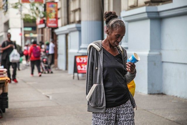 A homeless woman begs on 125th Street and Lexington Avenue on September 28, 2015. Issues with homelessness in Harlem have increased with the introduction and gaining popularity of K2, a drug marketed as synthetic marijuana.