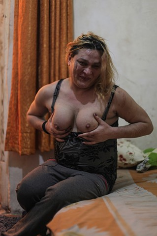 Angel, a transgender sex worker, sits on her bed in Istanbul, Turkey. She procures clients strictly online, as walking through the streets previously to find customers ended with her being burned with lit cigarettes and attacked at knifepoint.