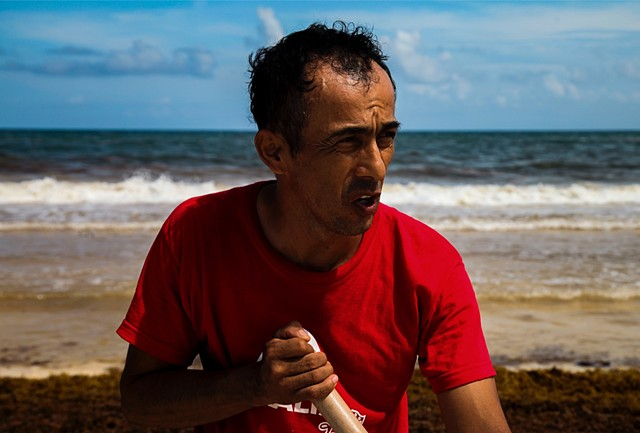 "Marc Antonio, one of just a few workers in charge of clearing the mounting seaweed at a small beach front hotel property, sweats in the afternoon sun in Tulum, Mexico. ""There's only three of us, and it gets worse every day. It's like we were never here."""