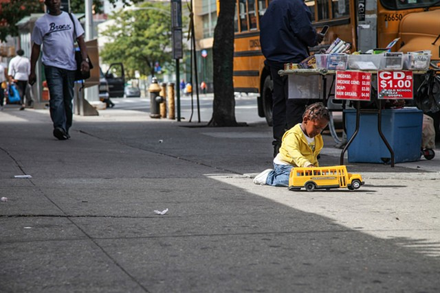 A young boy plays in the middle of 125th Street as his guardians sell items out of their car on September 28, 2015.