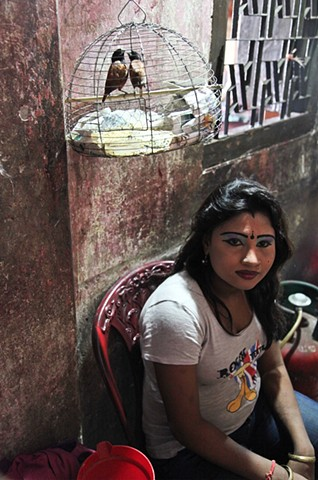 A young sex workers sits outside of her room with her pet birds at the Rathkhola Brothel in Faridpur, Bangladesh. The women put on elaborate makeup in the early afternoon to prepare for a long day of customers.