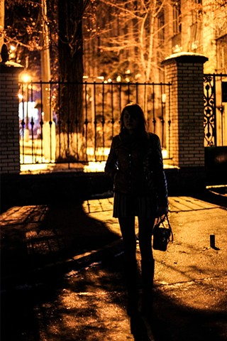 A sex worker, forced out of Donetsk by the conflict, stands in freezing temperatures along a main stretch of Kiev, Ukraine well known for prostitution. Her pimp watches her every move from a nearby building.