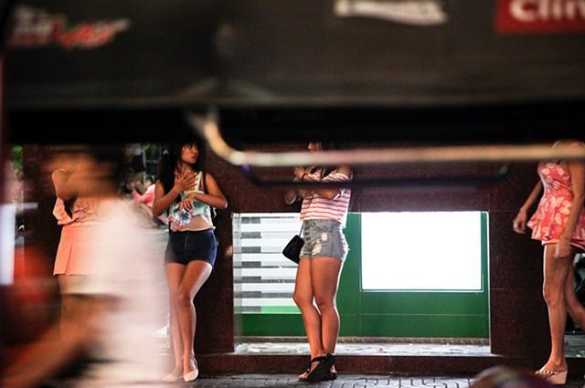 "Prostitutes wait on the street patiently for customers on Sukhumvit Soi 3 in Bangkok, Thailand. The street is a common attraction for American sex tourists seeking out ladyboys for the night, with hourly ""love"" hotels lining the streets."